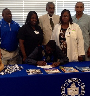 Kendrick Walk signing with Jackson State as family looks on.